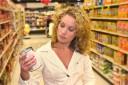 Frau liest Inhaltsstoffe der Ware beim Einkaufen